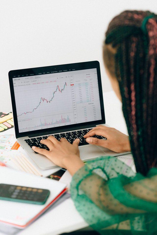 Imagem de mulher analisando dados de bolsa de valores no computador